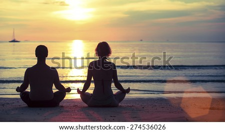 Silhouette of young couple practicing yoga on the Sea beach during beautiful sunset.