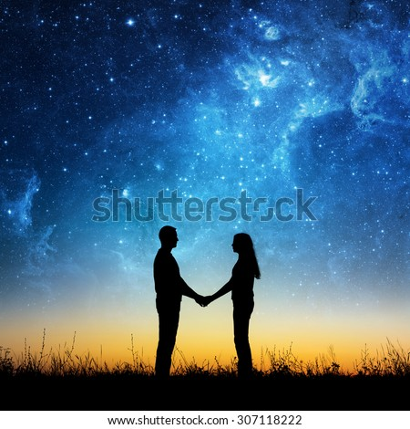Silhouette of young couple under stars. The concept on the theme of love. Elements of this image furnished by NASA. - stock photo