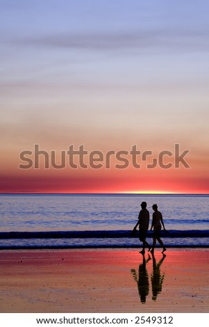 Silhouette of young couple walking on beach at sunset. This is Cable Beach, Broome, Western Australia