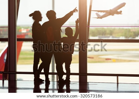 Silhouette of young family at airport - stock photo