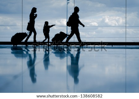 Silhouette of young family with luggage walking at airport, girl pointing at the window - stock photo
