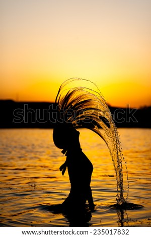 Silhouette of young fit woman posing standing in river playing with hair splashing water on sunset - stock photo