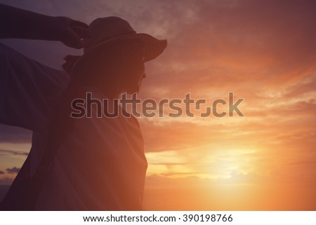 Silhouette of young girl in hat looking far away at sunset (intentional sun glare and vintage color) - stock photo
