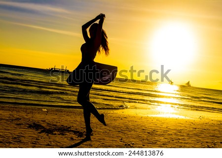 silhouette of young happy woman on sunset sea and beach background - stock photo