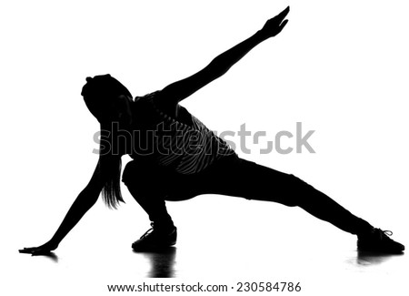 Silhouette of young hip-hop dancer woman is showing some moves on the grey background. - stock photo
