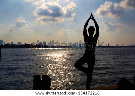 silhouette of young male involved in yoga on background sunset in Miami. - stock photo