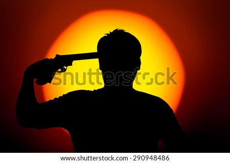 silhouette of Young man commits suicide with his revolver gun - stock photo