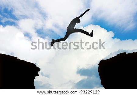 Silhouette of young man jumping over a cliff - stock photo