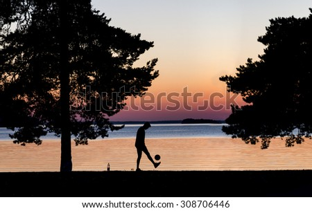 Silhouette of young man kicking football on beach at sunset