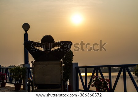 Silhouette of young man relaxing on wheelchair with sunset against river background - stock photo