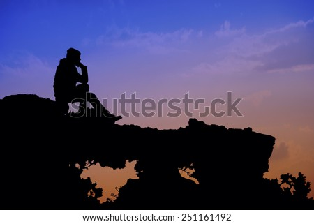 Silhouette of young man sitting on a rock  - stock photo