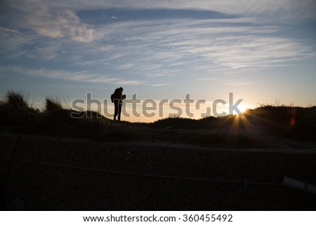 Silhouette of Young Man Watching His Camera In Front of the Sunset.