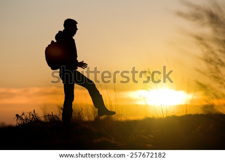 Silhouette of young man with backpack making step in nature