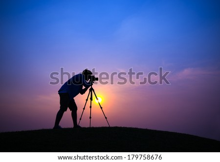 Silhouette of Young Photographer at Sunset - stock photo