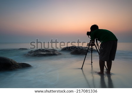 Silhouette of young photographer on the beach. - stock photo
