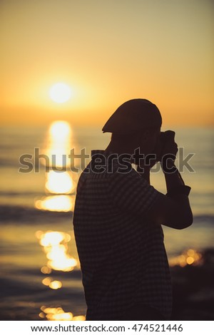 Silhouette of young photographer on the beach takes pictures of the sunset over the sea.