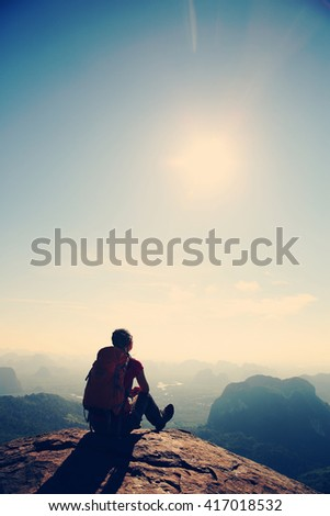 silhouette of young successful woman hiker on mountain peak