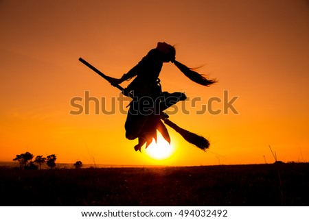Silhouette of young witch flying on the broomstick against sunset