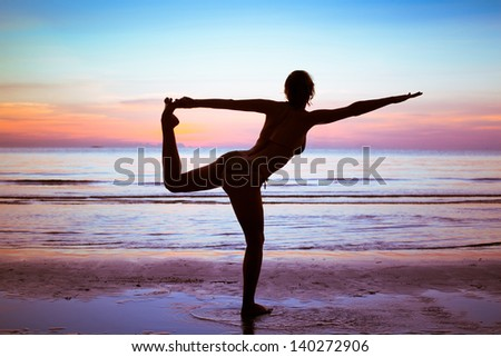 silhouette of young woman doing gym and stretch exercises on the beach - stock photo