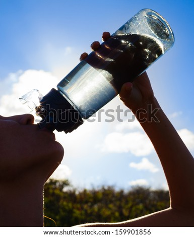 Silhouette of young woman drinking water - stock photo