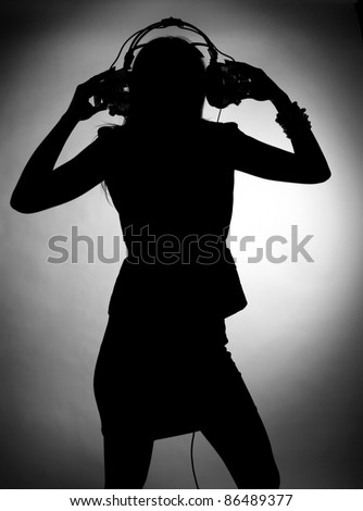 Silhouette of young woman enjoys listening music in headphones. Classic monochrome photography. - stock photo