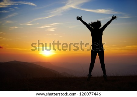 Silhouette of young woman jumping against sunset with blue sky - stock photo