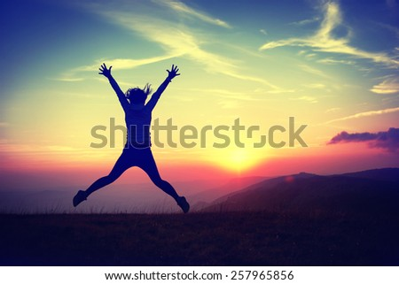 Silhouette of young woman jumping against sunset with blue sky. Colorized like instagram