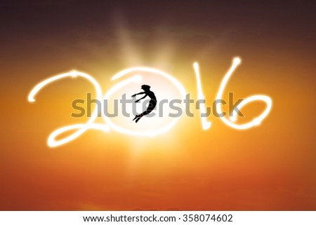 Silhouette of young woman jumping on the air while celebrating new year of 2016 - stock photo