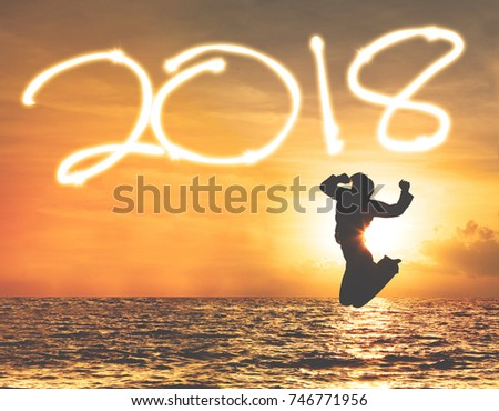 Silhouette of young woman jumping on the beach with numbers 2018 on the sky