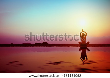 Silhouette of young woman practicing yoga on the beach at sunset - stock photo
