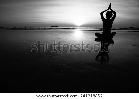 Silhouette of young woman practicing yoga on the sea beach. Black and white high contrast photography. - stock photo