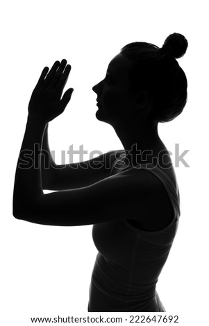 Silhouette of young woman praying against white background - stock photo