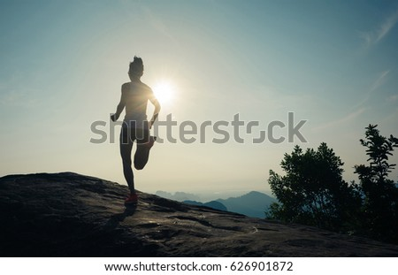 silhouette of young woman running on sunrise mountain peak
