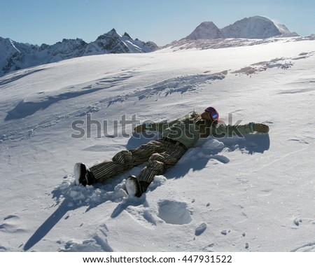 Silhouette of young woman snowboarder, lying down on snow, moving her arms and legs up and down creating a snowy angel figure at the ski resort of Elbrus