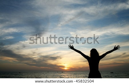 silhouette of young woman standing at the beach - stock photo
