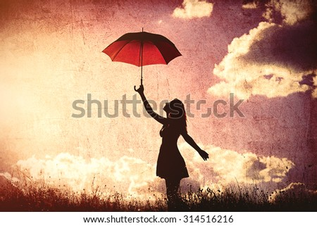 Silhouette of young women with umbrella on sky background - stock photo