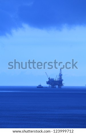 Silhouette Offshore Jack Up Drilling Rig and Boat (BlueTone) - stock photo
