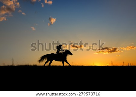 Silhouette or woman and horse running across horizon as the sun goes down. - stock photo