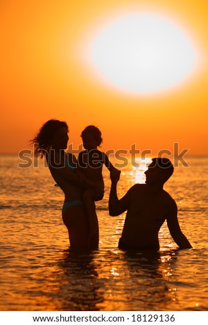 silhouette Parents with child in sea on sunset