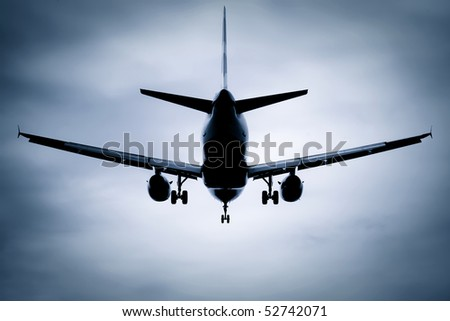 silhouette passenger jet on takeoff or landing through soft focus clouds - stock photo