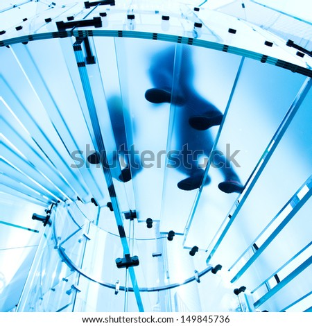 Silhouette people on glass staircase - stock photo