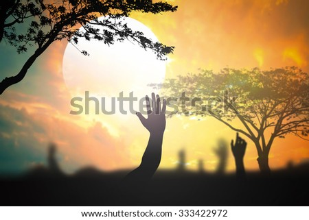 Silhouette people raising hands on blurred beautiful golden autumn sunset background. Christmas, Forgiveness, Mercy, Repentance, Adoration, Glorify, Redeemer, Redemption, Gospel, resurrection concept. - stock photo