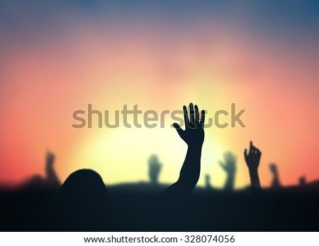 Silhouette people raising hands over blurred autumn sunset background. - stock photo
