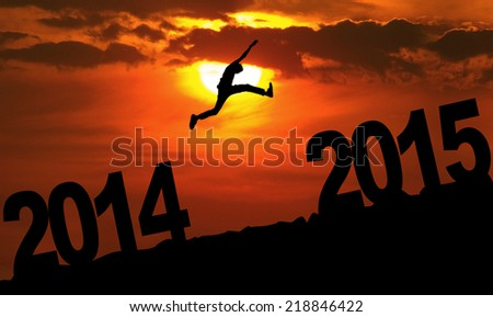 Silhouette person jumping over 2015 on the hill at sunset - stock photo