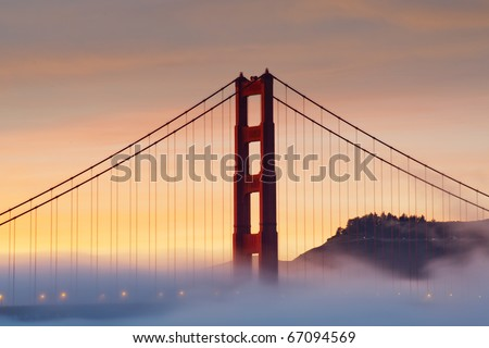 Silhouette photo of Golden Gate bridge emerge from the fog with beautiful sunset - stock photo