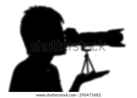 silhouette photographer holding camera  - stock photo