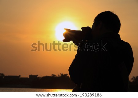 Silhouette photographer in dawn light - stock photo