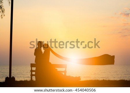 Silhouette picture of the bride and groom wedding over blurred beautiful nature pastel.wedding and lovers concept. - stock photo