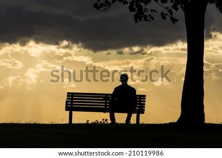 Silhouette portrait of a lonely anonymous man sitting on a bench watching the dark skies above roll by.  - stock photo