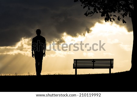 Silhouette portrait of an anonymous man walking away from a bench as dark clouds roll above him. The sun behind creating light between the clouds - stock photo